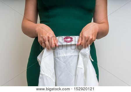 Woman Holding A Shirt With Lipstick Of Her Unfaithful Husband