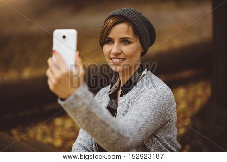 Portrait of smiling and happy young millenial woman sitting alone in the forest, taking selfie and posting to social media with smartphone. Broadband mobile internet connection