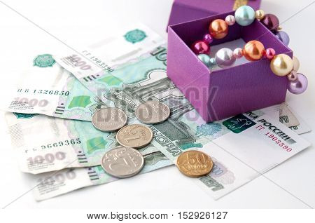 Pearl necklace in gift box stands on thousandths bills and coins