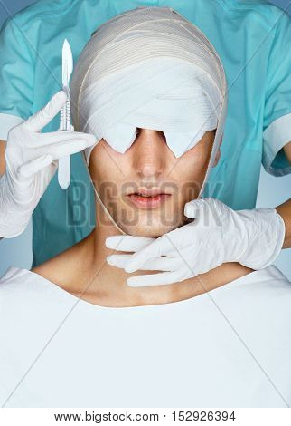 Patient with medical Bandage on his Eyes after cosmetic operation. Close up of bandaged face before Plastic Surgery. Beauty concept.