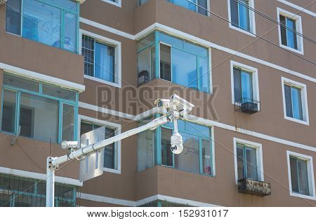 Close up view on traffic cameras on background of facade of appartment building with windows and balconies