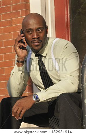 Businessman having conversation on smart phone outside his office