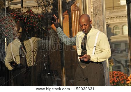 Sharp businessman checking messages on mobile phone in the city