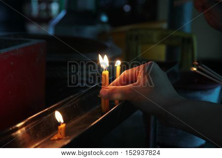 Buddhists make merit,Placing a lighted candle on the altar of Buddha at temple. Selective focus.