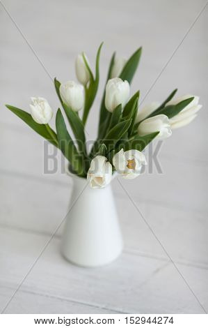 White tulips in a vase on a white background. Spring background. Spring mood. White flowers in a vase.