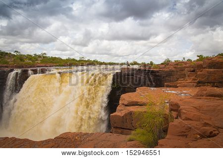 A closeup up of the top drop of the Eastern falls flood with a photographer on one side giving a sense of scale at the King George River in the Northern Kimberley of Western Australia