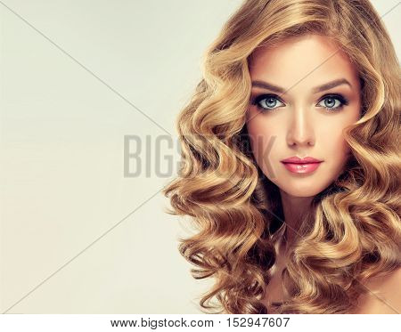 Beautiful girl with long wavy hair . Blonde with curly hairstyle . jewelry earrings  and bracelet