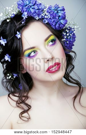 Beauty young woman with flowers and make up close up, real spring beauty girl floral blue