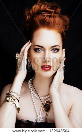 beauty stylish redhead woman with fancy hairstyle and manicure wearing jewelry pearl close up