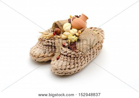 Bast shoes with products on a white background. The symbol of hearth and wealth.