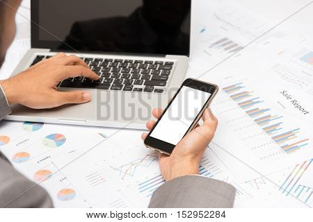 Businessman holding blank smartphone mobile while using laptop on table with graphs and charts at office.