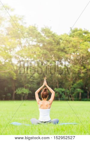 Girl do yoga pose at the park in the morning with sunlight.