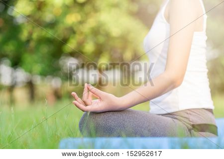 Girl do yoga at the park in the morning.
