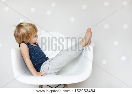 Happy And Playful Cute Little Two-year Boy Dressed In Pajamas Sitting On White Chair In Studio Of Ph