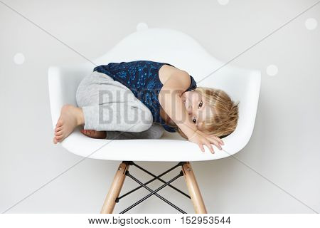 Children And Happiness Concept. Cozy Shot Of Beautiful Two-year Old Infant Lying On White Chair, Rol