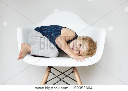 Childhood And Leisure Concept. Sweet Adorable Two-year Old Toddler With Cute Smile Curling Up In Whi