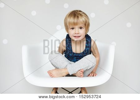 Portrait Of Cute Caucasian Infant With Blonde Hair And Big Beautiful Eyes Dressed In Sleeping Suit,