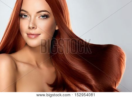 Beautiful girl with long shiny straight red hair . Care and hair products .