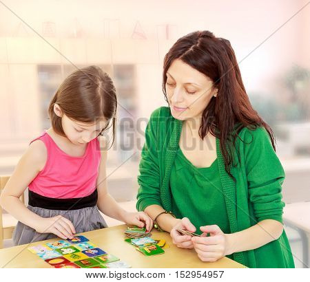 Cute little girl and her mother at the table laid out cards with pictures.During a lesson in school.