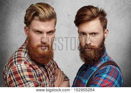 Two Young Caucasian Handsome Brothers Posing Together Indoors. Fashionable Hipster Models With Thick