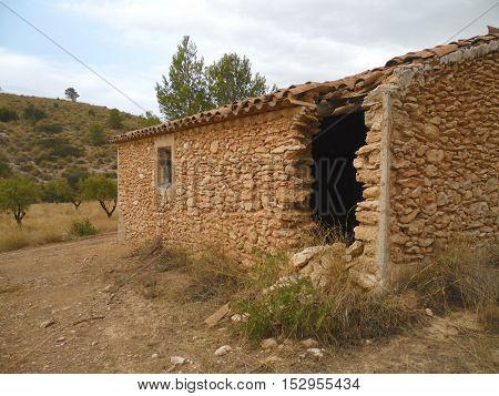 cortijo abandonado construido en ladrillo y piedra
