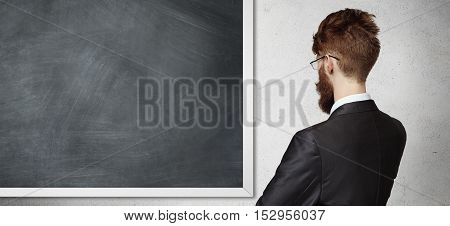 Back View Of Young Employee Wearing Formal Suit And Glasses, Standing In Front Of Blackboard, Presen