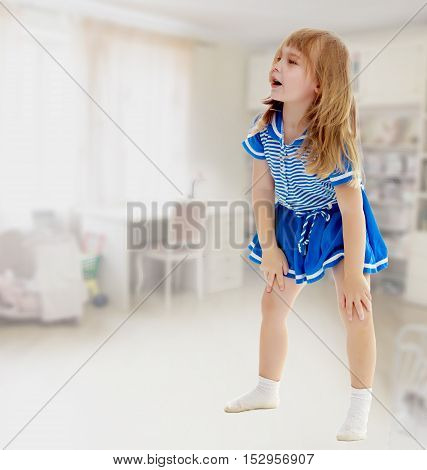 Cute little unkempt girl in a short blue dress. Girl looking to the side with his hands on his knees.In the rooms, with a Desk and long shelves on which stand toys.