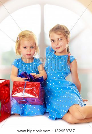 Two charming little girls , sisters, in identical blue dresses with polka dots. Girl looking at gifts Packed in beautiful red paper tied with a bow.Against the background of a child's room .