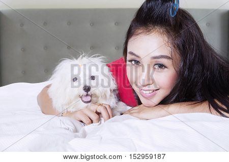 Image of Beautiful girl with cute puppy while lying on the bed