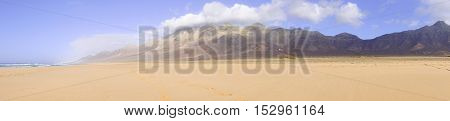 Landscape with ocean golden sand and mountains on a famous beach Cofete on the Canary Island Fuerteventura Spain.