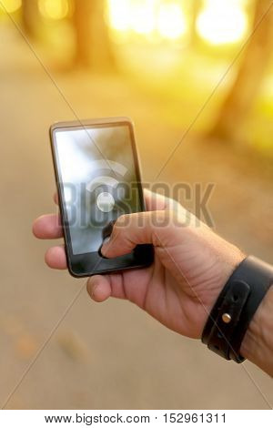 Man searching for mobile GPS signal in woods male hand holding smart phone device with poor connection signal displayed. Outdoors connectivity concept and weak or no network symbol on screen.