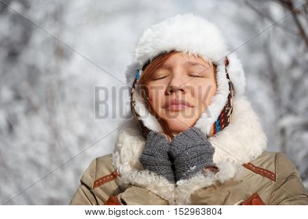 Beautiful young smiling woman in gray fingerless knitted mittens cap with ear flaps and coat with white fur at the background of snowy forest.
