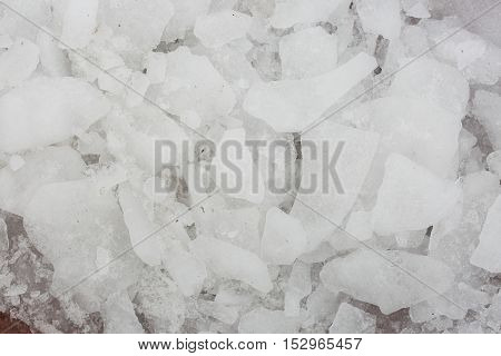 Ice on asphalt. Texture of ice. Frozen snow. The split ice. Pieces of ice.