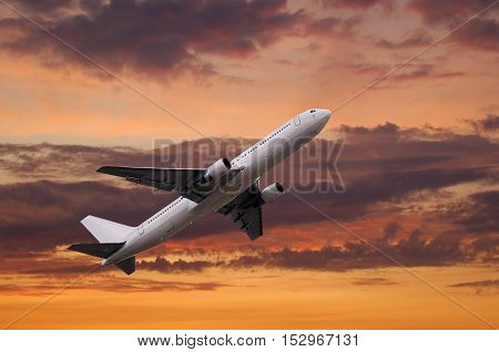 airplane taking off on red dramatic sunset cloudscape
