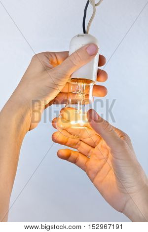hands with glowing incandescent light bulb closeup