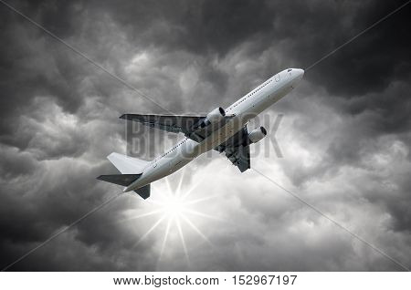Airplane above the Sun shining from Darkclouds of storm sky