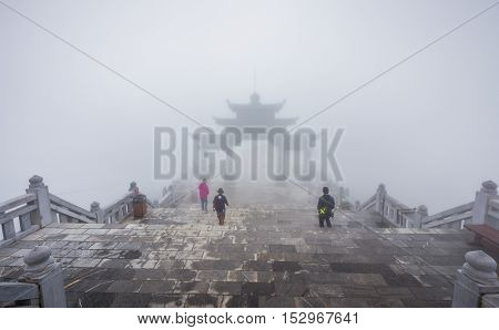 Sa Pa Vietnam - September 18 2016: People walking down to Big gate on ladders of Fansipan legend of Sa Pa Vietnam environment cover by fog and mist.