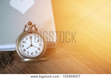 Pocket watch over the book on wooden table with light flare and copy space