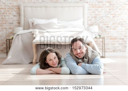 Being in a bedroom. Positive nice young couple crossing their arms and smiling while lying on the floor in front of the bed
