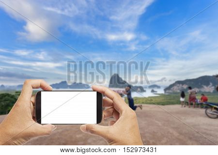 Hand male asian holding Smartphone taking picture of beautiful landscape view in phang-nga thailand