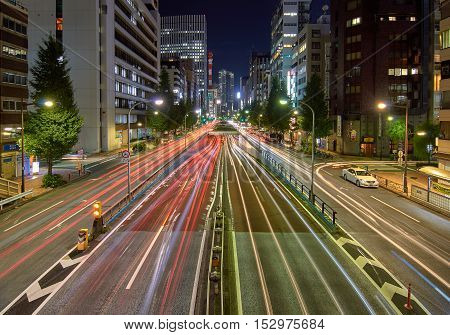 Tokio, Japan - Setember 5, 2016: Car light trails in a busy wide avenue with a tunnel in the middle and illuminated buildings on the background.