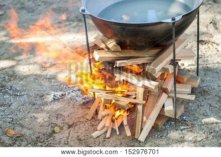 Cooking on a fire. Food in a cauldron on a fire. Food outdoors. Cooking outdoors. Cooking in nature on the cauldron. Water in copper on fire.