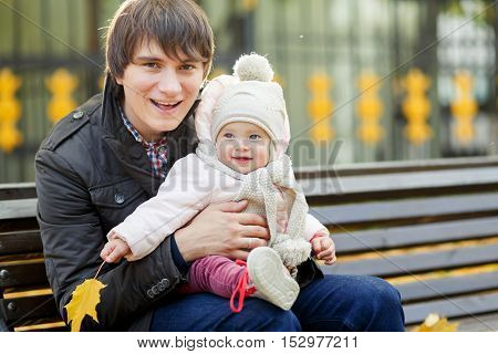 Young dad with his little daughter sitting on bench in autumn park