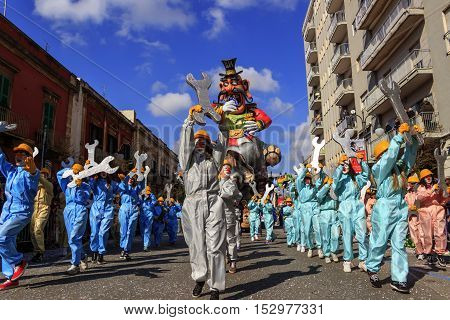 Putignano, Apulia, Italy - February 15, 2015: Carnival floats, giant paper mache. Carnival costume: allegorical float of Ilva industry.