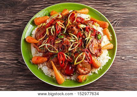 takeaway classic pork on rice with fried in sticky sauce carrots, sprinkle of chili and spring onion