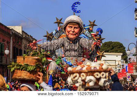 Putignano,Apulia,Italy - February 15, 2015: carnival floats, giant paper mache. European politician: Angela Merkel. Carnival Putignano: floats. Angela Merkel torture the European Union.