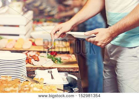 Midsection of man at breakfast buffet in hotel