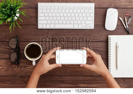 hand holding phone horizontal showing phone blank screen on work table mock up phone rose gold color