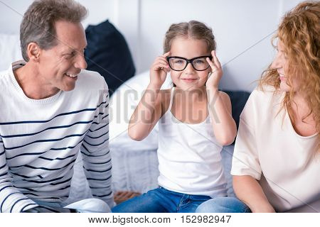 Look at my glasses. Cute little girl sitting on the bed with her grandparents while wearing glasses and having fun at home