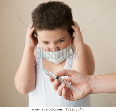 hand with syringe in front of thick scared boy in the medical mask